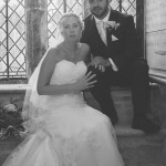 Bride and groom sitting in front of stained-glass church windows