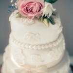 White wedding cake with flower adornment on top