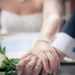Bride and groom hold hands during marriage certificate signing