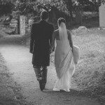 Wedding couple walking away from camera, into cemetary, black and white