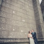 Couple lean against church wall
