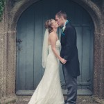 Wedding couple kiss in front of blue door