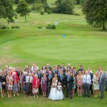 Wedding guests stand in golf course